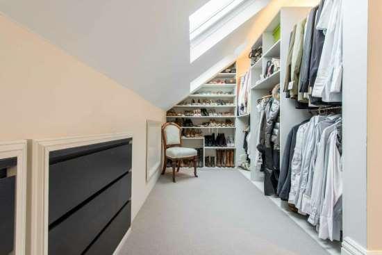 Плюсы гардеробной в мансарде со скошенным потолком
